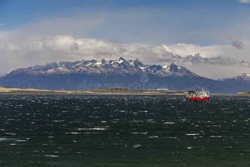 Seelandschaft mit einem Schiff auf großem majestätischem Schneegebirgshintergrund Spürhund-Kanal, Ushuaia, Argentinien lizenzfreie stockfotografie