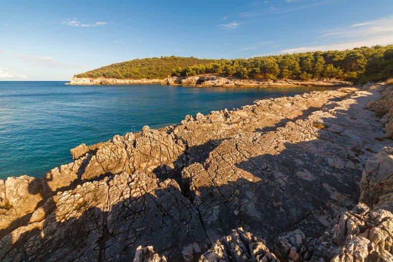 Seelandschaft mit Felsen, Klippen und Wald an einem sonnigen Sommertag kroatien lizenzfreie stockfotografie