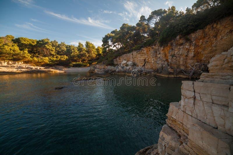 Seelandschaft mit Felsen, Klippen und Wald an einem sonnigen Sommertag kroatien lizenzfreie stockbilder