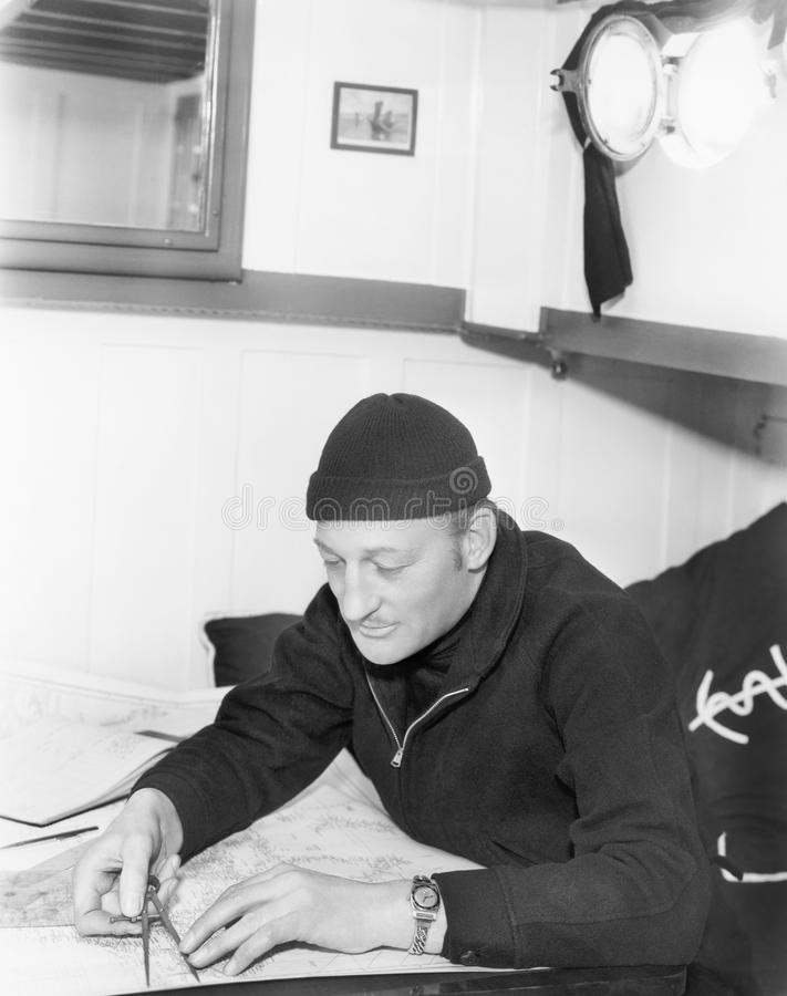 Seemann, der über einer Karte mit einem Kompass schaut (alle dargestellten Personen sind nicht längeres lebendes und kein Zustand stockfotografie
