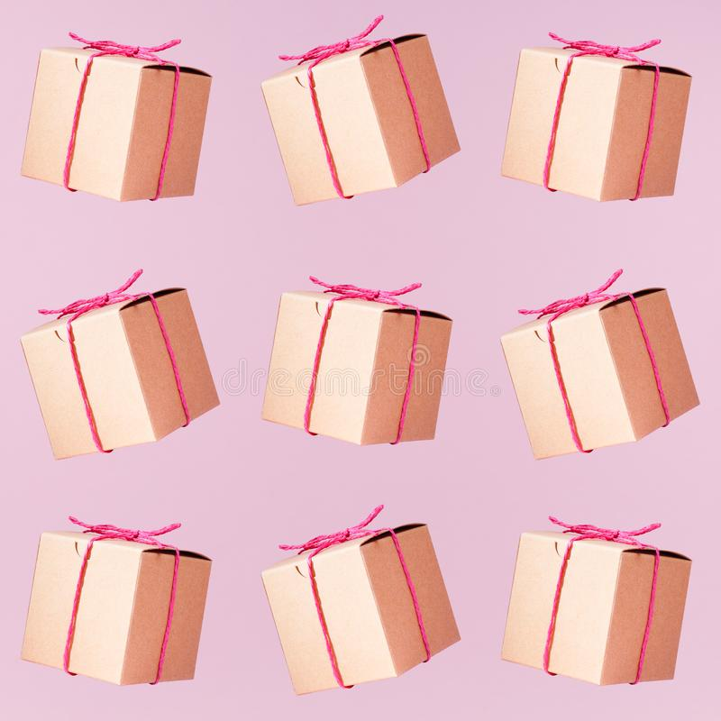 Seemless pattern of craft cardboard gift boxes on the solid pink royalty free stock photography