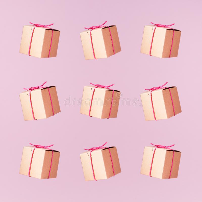 Seemless pattern of craft cardboard gift boxes on the solid pink royalty free stock photos