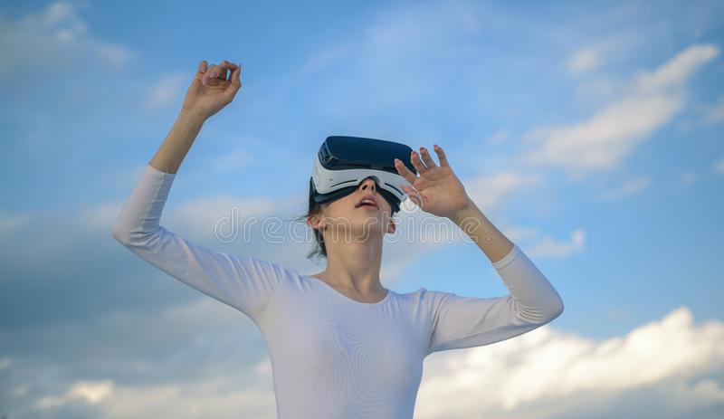 It seems so real. Cute girl play in simulated environment. Young woman gesturing in vr glasses. Pretty girl wear virtual stock image