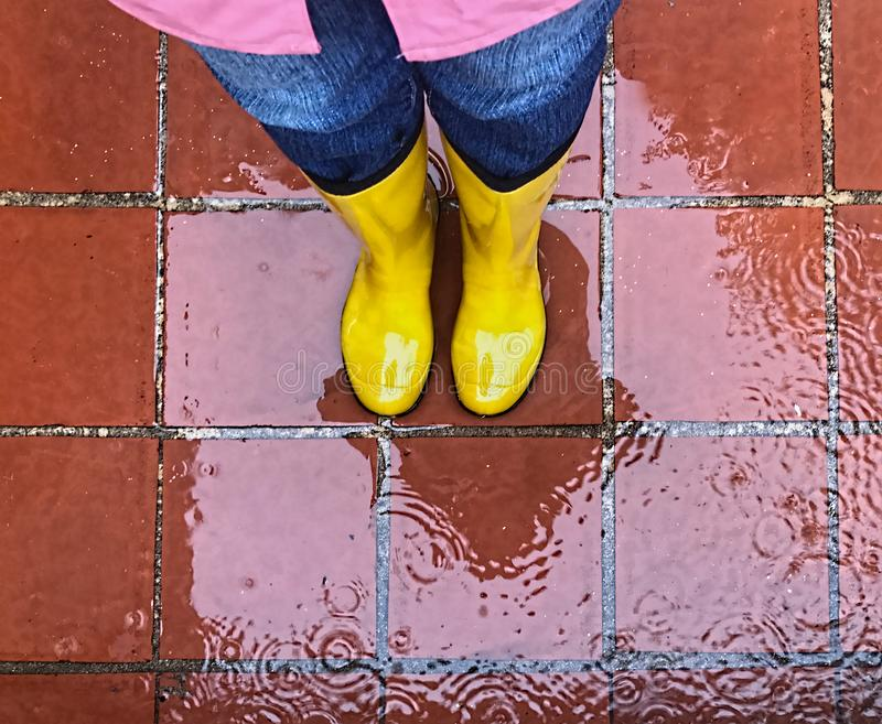 Aerial view of bright, yellow rubber rain boots on wet tiles. Seen from above, is a pair of yellow, rubber, rain boots and legs standing on a wet tile surface royalty free stock photo