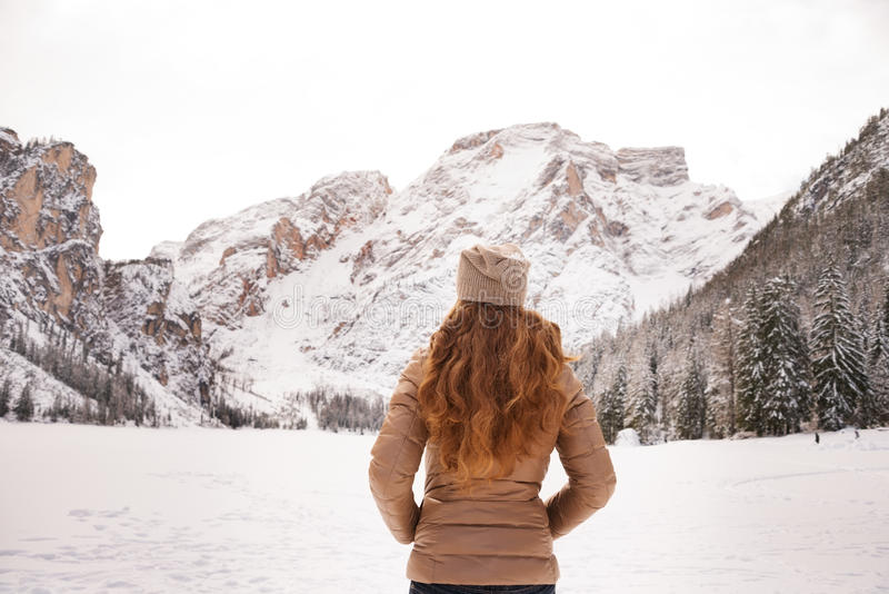 Seen from behind woman outdoors among snow-capped mountains royalty free stock photos