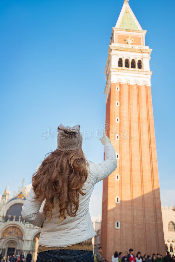 Seen from behind woman pointing on tower of St Marks Basilica royalty free stock images