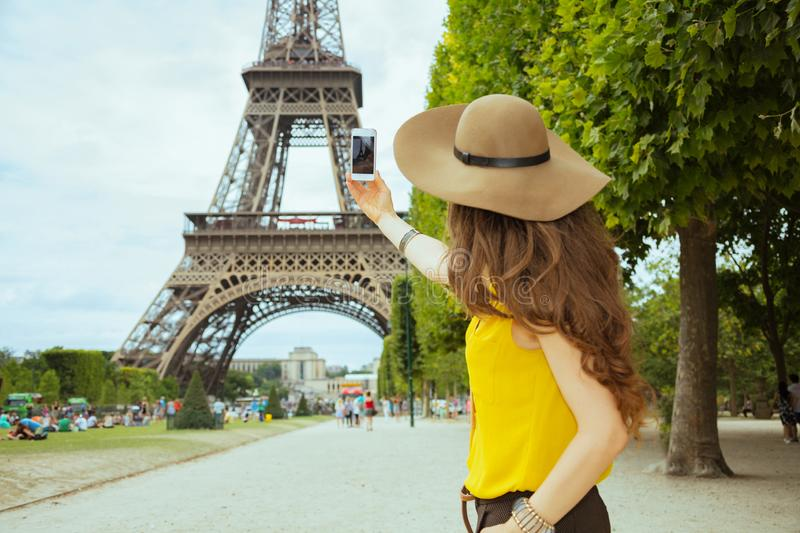 Young solo tourist woman taking photo with smartphone. Seen from behind young solo tourist woman in yellow blouse and hat taking photo with smartphone against royalty free stock photos