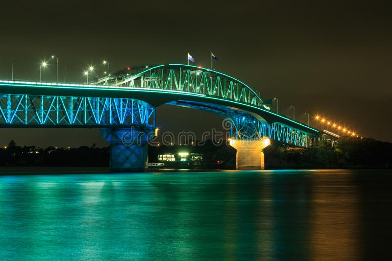 Auckland Harbour Bridge, New Zealand, with vivid green and blue lighting. Seen from the southern end, Auckland Harbor Bridge is shown here brightly illuminated royalty free stock images
