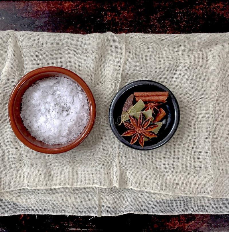Seesalz, Sternanis, Lorbeerblatt, schwarzes Kardamom und Zimtstange vereinbarten in zwei kleinen Schüsseln auf Seihtuch stockbild