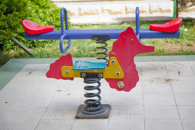 Seesaw on child playground in park. childs horse ride in the playground .Swing on a metal spiral . Spring horse in the playground royalty free stock photography