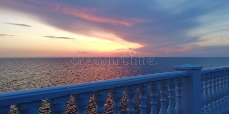 Seesonnenuntergang-Herbstlandschaft in den blauen und rosa Tönen vor dem hintergrund einer weißen Balustrade Sch?ner interessante stockbild