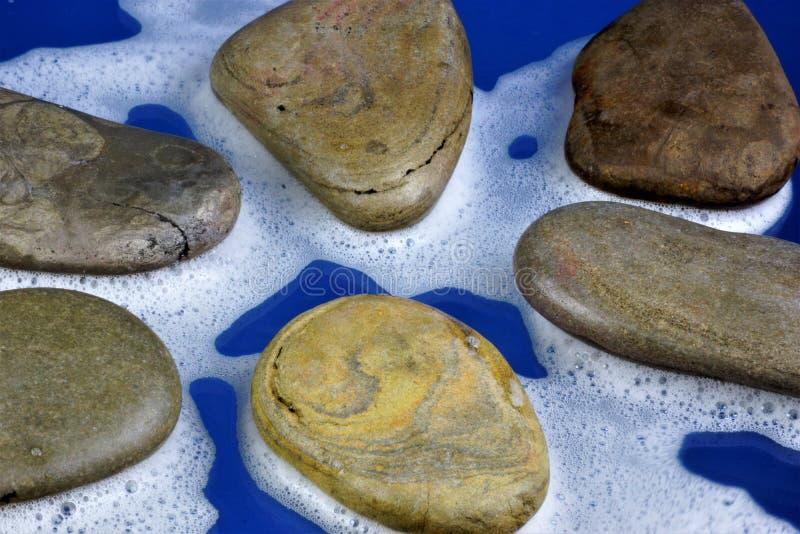 Seesteine im wei?en Schaum, wasser-durchn??te Fragmente von Steinen des nat?rlichen Ursprung, auf einem blauen Hintergrund Steine lizenzfreies stockbild
