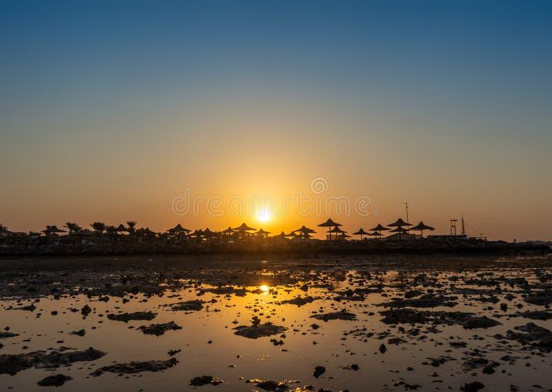 Seestrand während der Ebbe mit nackter sandiger Unterseiten- und Strandausrüstung auf dem Ufer auf dem Sonnenuntergang - Ägypten lizenzfreie stockfotografie