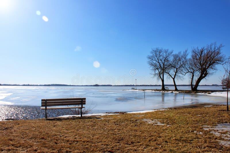 Seeufer-Bank durch gefrorenen See lizenzfreies stockfoto