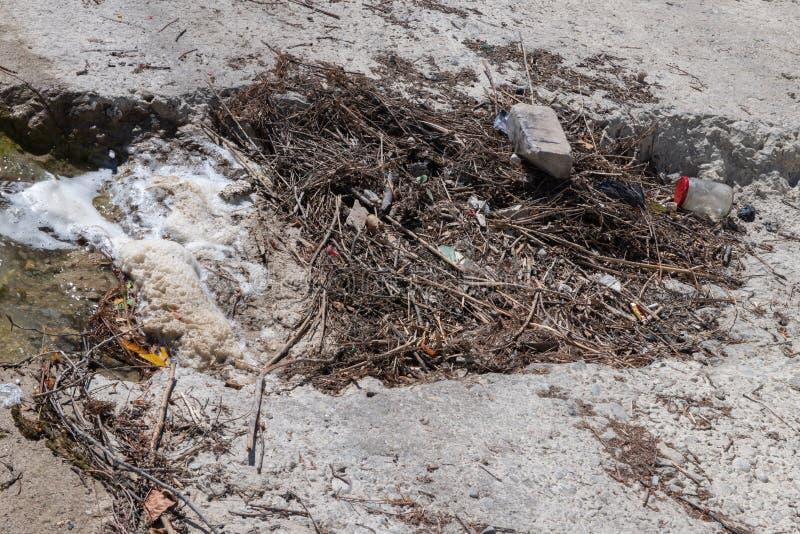 Seeufer mit Abfall und Schaum stockfoto