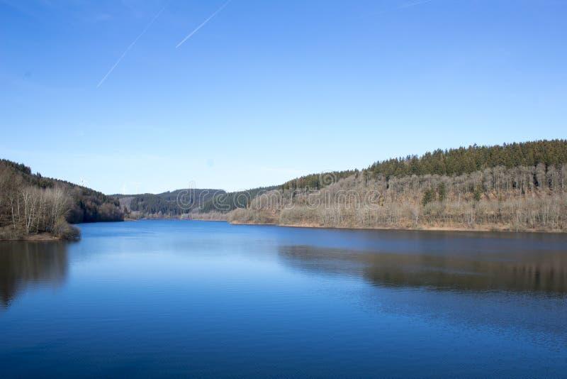 Seeuferansicht mit perfektem blauem Wasser lizenzfreie stockfotos