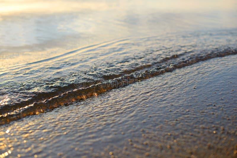 Seewelle und Sandküste Goldenes Sonnenlicht über den Seemeereswogen stockfotografie