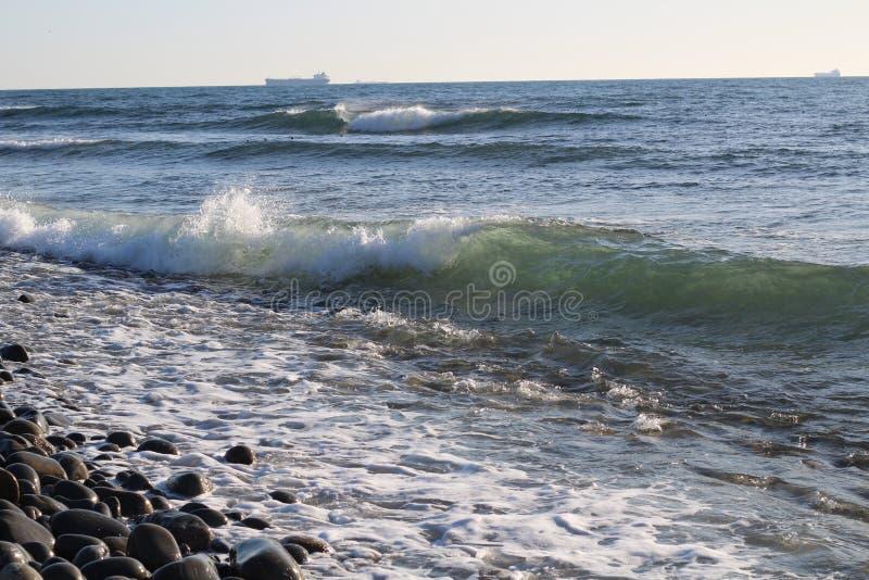 Seewelle und steiniges Ufer lizenzfreie stockbilder
