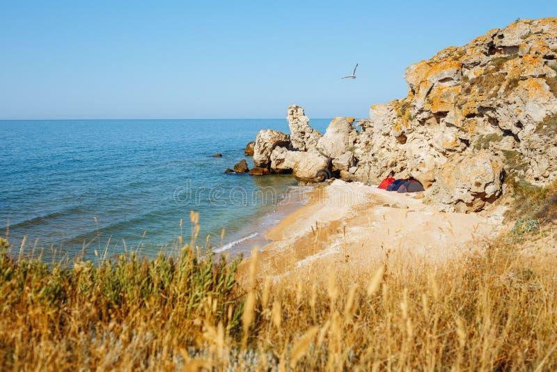 Seewilde Bucht in den Felsen mit drei Zelten Steine im Ozeanwasser stockbilder