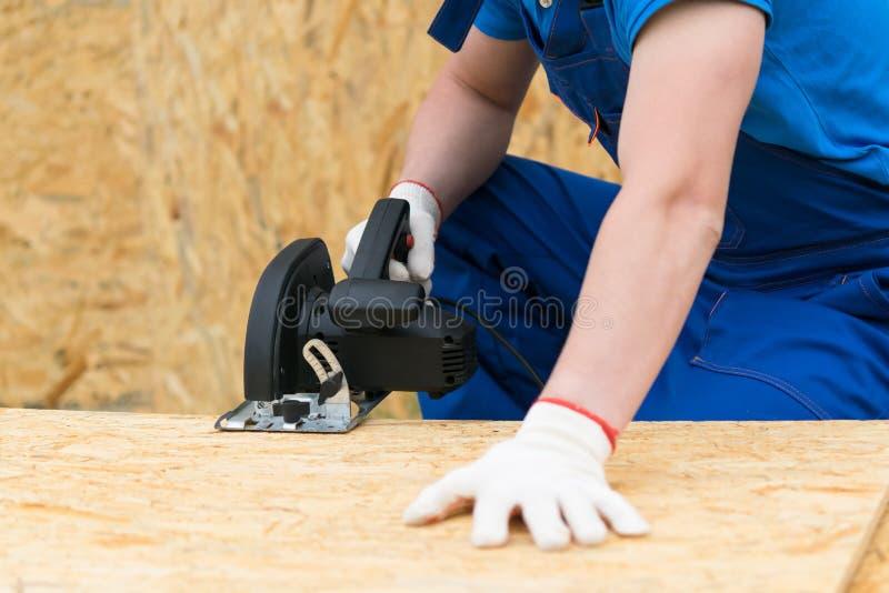 Sega circolare nelle mani di un uomo che sega una plancia di legno, primo piano fotografia stock libera da diritti