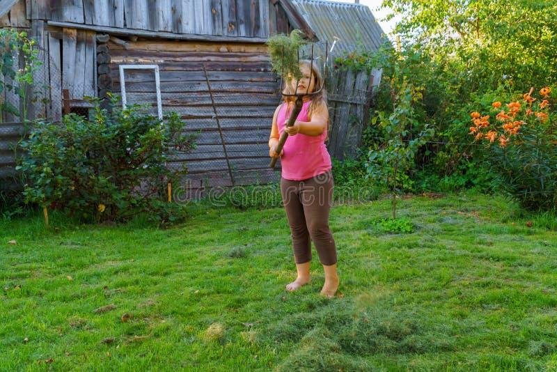 Segando a una niña la hierba de la manera tradicional del pueblo con la guadaña fotos de archivo