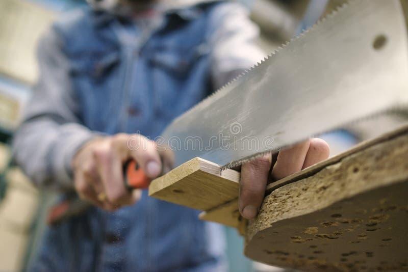 Segare un bordo di legno con la sega di mano o il seghetto a mano per metalli giapponese speciale durante la carpenteria fotografia stock libera da diritti