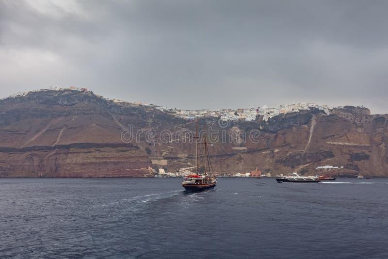 Segelbåtöverskrift in mot porten av den Fira byn, Santorini ö royaltyfri bild