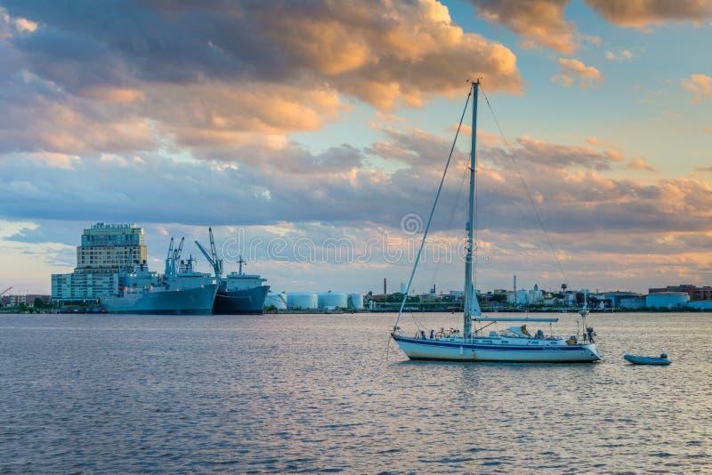 Segelbåt i hamnen och sikten av silopunkt på solnedgången, i kanton, Baltimore, Maryland arkivbilder