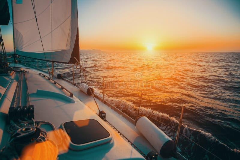 Segelbåt i havet under enorm solnedgång royaltyfri fotografi