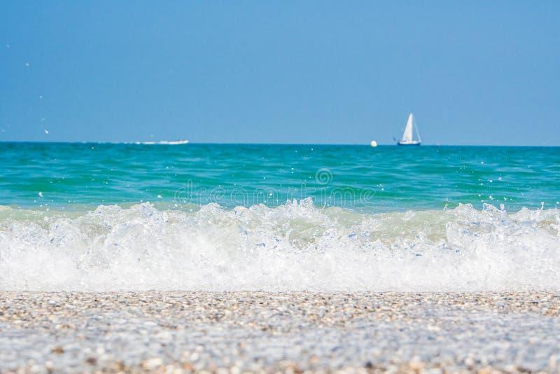 Segelbåt med blå himmel, turkoshavet och kusten mycket av kiselstenar arkivfoto