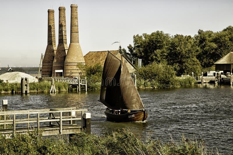 Segelbåt och fabrik arkivfoton