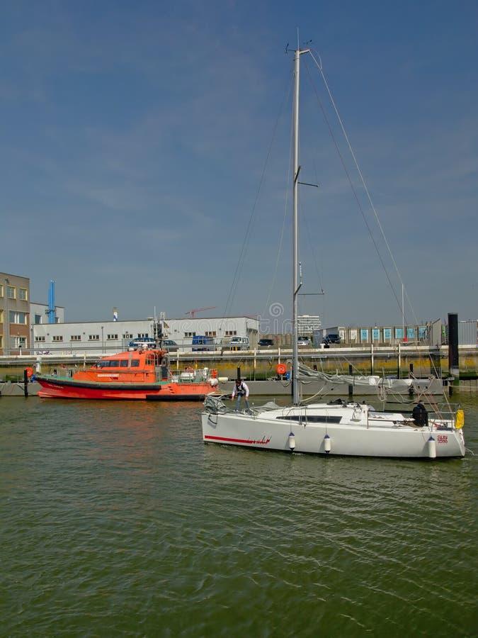 Segelbåt och räddningstjänstfartyg i hamnen av Ostend, Belgien fotografering för bildbyråer