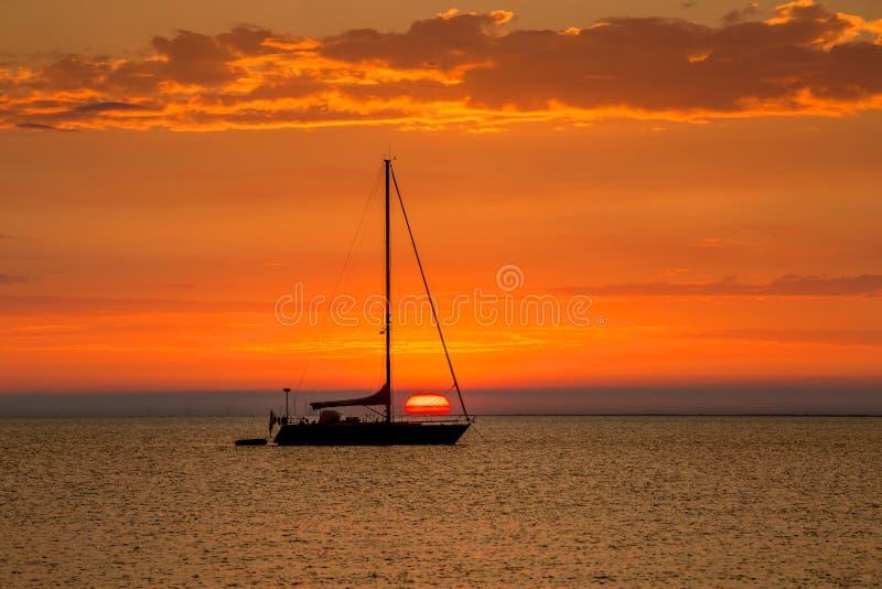 Segelbåt på ankaret med härlig solnedgång i bakgrunden royaltyfri bild