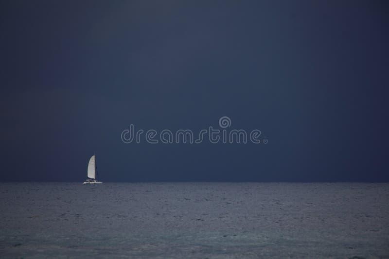 Segelbåt på det öppna havet på natten arkivbilder