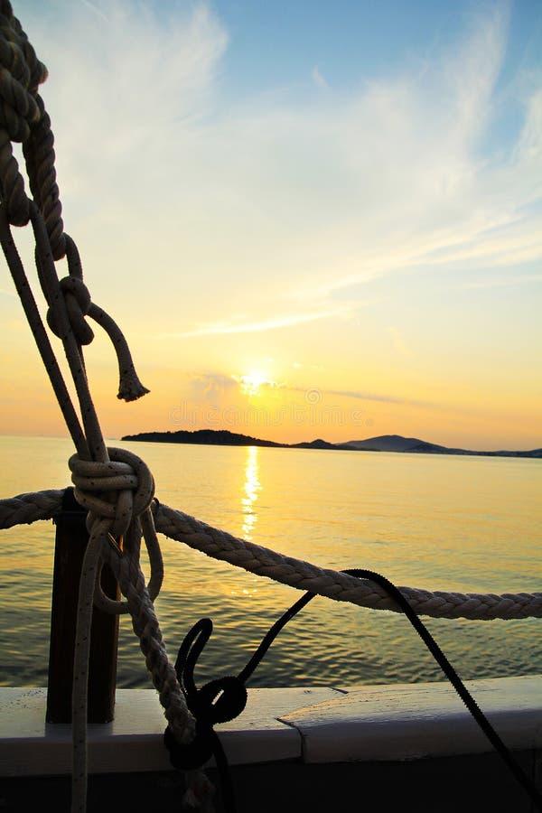 Segelbåt på det lugna havet framme av att blekna gul solnedgång royaltyfri bild