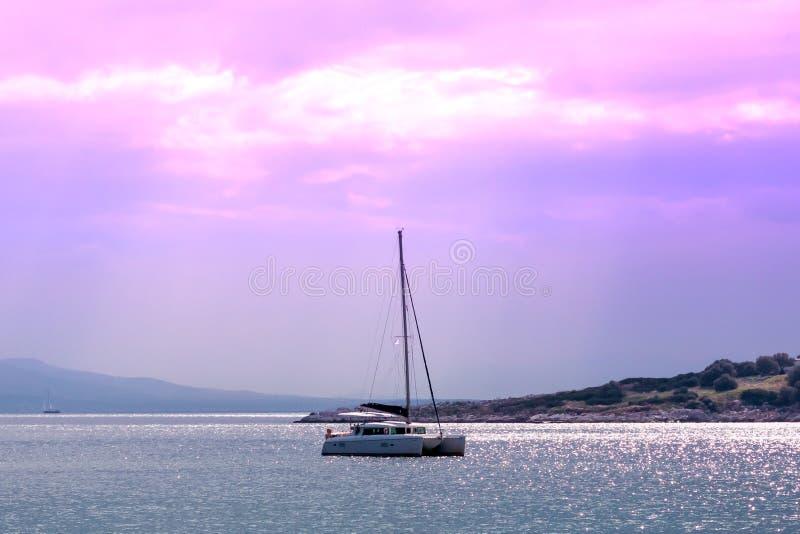 Segelbåt på havet på solnedgången Sommarafton på en ö i Grekland royaltyfri fotografi