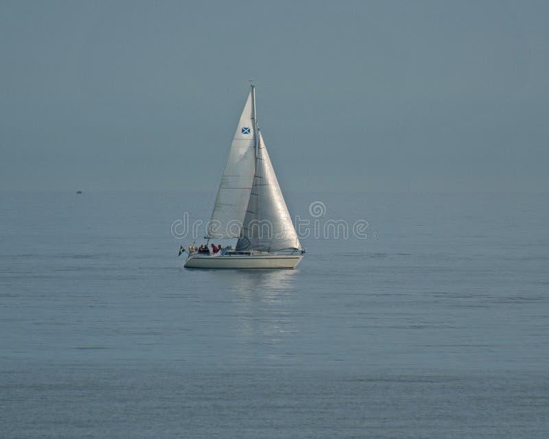 Segelbåt på lugna vatten arkivbild