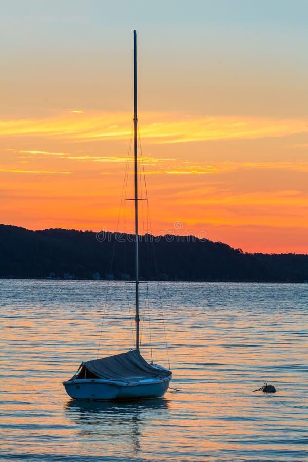 Segelbåt på sjön på gryningen royaltyfri foto