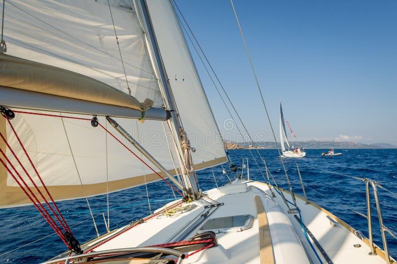 Segelbåt som går snabb på she& x27; s seglar, sikten från cockpiten för att buga royaltyfri fotografi