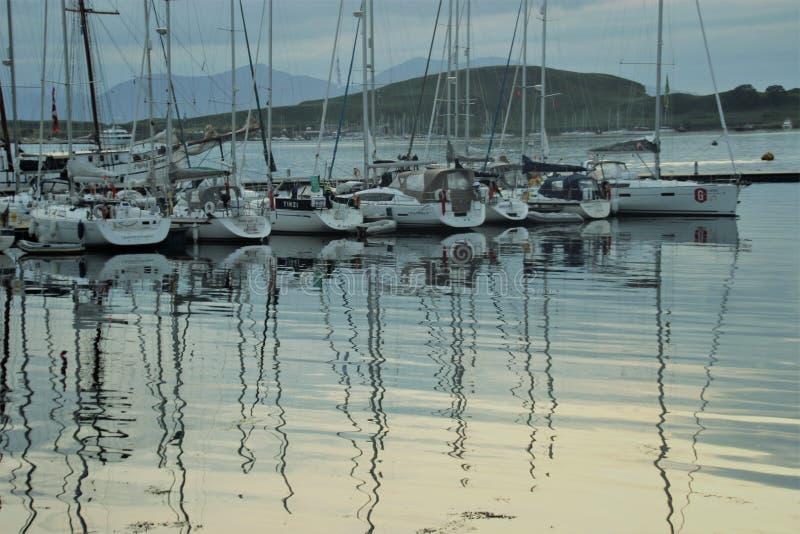 Segelbåtar i marina, i aftonljus I fjärden av Oban Skottland royaltyfri foto