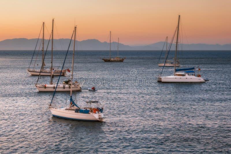 Segelbåtar på solnedgången i medelhavet av kusten av Mandraki härbärgerar Rhodes ö Grekland arkivfoton