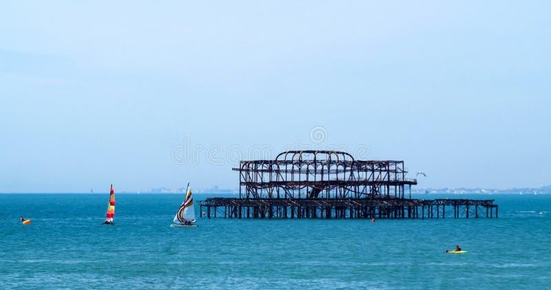 Segelbåtar runt om den övergivna västra pir i Brighton arkivbilder
