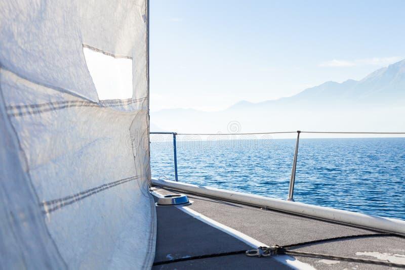 Segelbåten i solig dag i sjön, tömmer utrymme arkivfoto