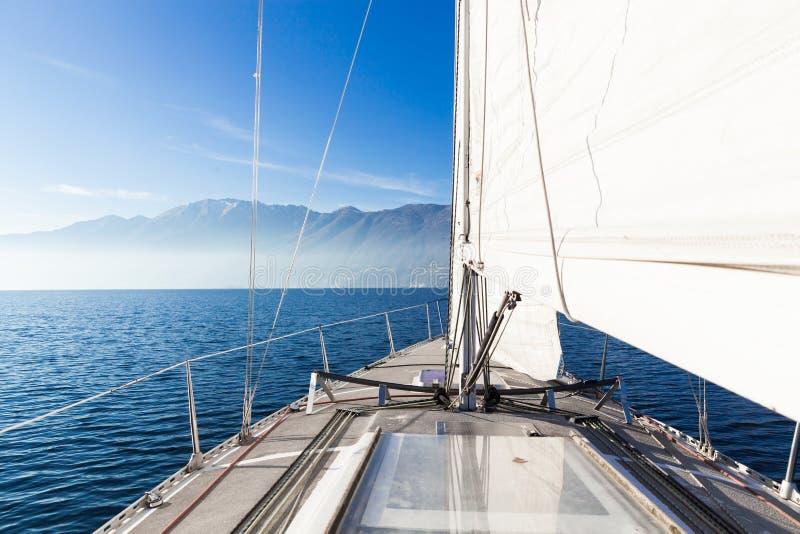 Segelbåten i solig dag i sjön, tömmer utrymme royaltyfri bild