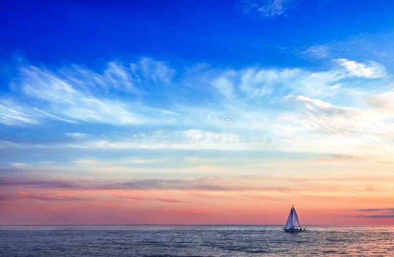 Segelbåten seglar under inställningssolen royaltyfri fotografi