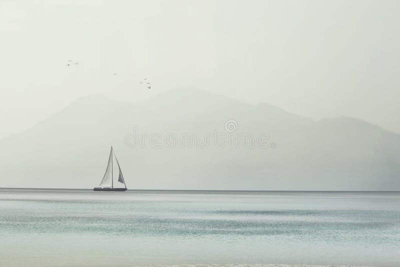 Segelbåtglidljud lätt på vågorna av ett spektakulärt hav royaltyfri foto