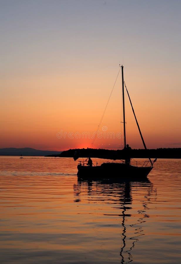 Segelbåtsilhouette på solnedgången arkivbilder