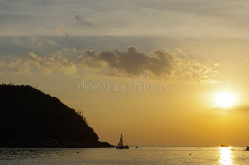 Segelbåtsolnedgångfantasin är en skyttelsegling med mycket seglar öppet silhouetted mot en färgrik orange solnedgånghimmel royaltyfria bilder