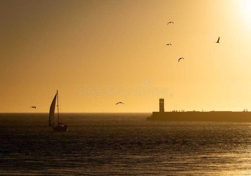Segelboot-Ansätze Farol tun Pontao an der Dämmerung lizenzfreie stockbilder