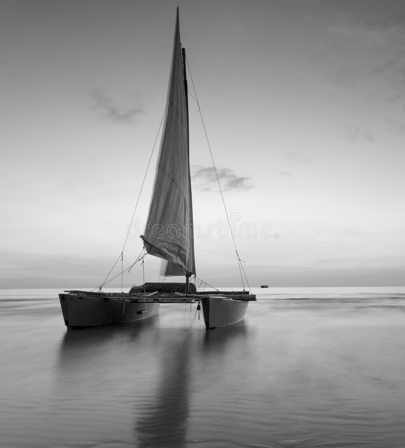 Segelboot auf dem Strand mit einem schönen Sonnenuntergang in Schwarzweiss stockfotografie